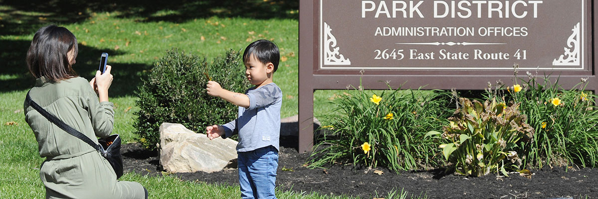 Child in front of park district sign