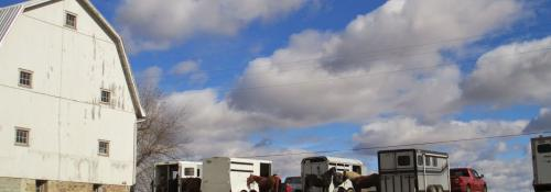large view of blue sky, barn and horse trailers